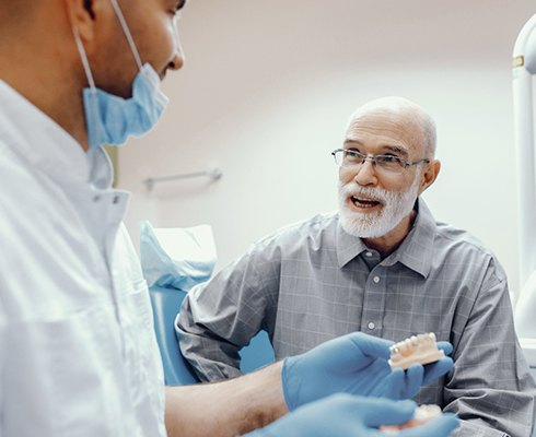 Dentist talking to male patient about dentures in Uniontown